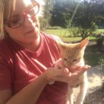 Trina holding kitten who's eating treats from hand.
