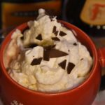 Southern Loaded Hot Chocolate - Close up cup full with whipped topping and chocolate chunks.
