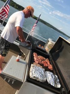 Robert grilling on Sikes Grill on top of the boat at Greers Ferry.