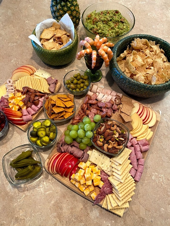 This is how to make a charcuterie board on vacation with meat, cheese, crackers, nuts, fruit and relish items on the side.
