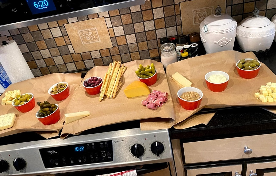 How to make a charcuterie board by placing relish, condiment and dip dishes first when assembling.